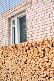 Drewno opałowe przy ścianie wiejskiego budynku