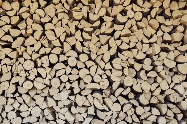 Drewno opałowe ścienne. tło suchych posiekanych kłód drewna opałowego w stosie
