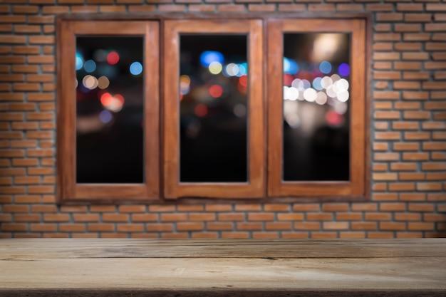 Drewno podłoga lub stół na okna drewniane i cegła ściany z nocnym świetle tła miasta