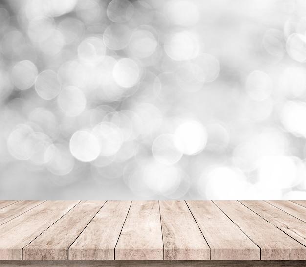 Drewno stół lub drewniana podłoga z abstrakcjonistycznym białym lub srebrnym bokeh tłem dla produktu pokazu
