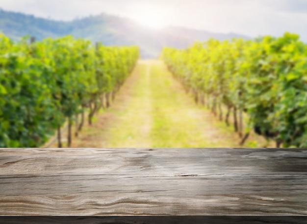 Drewno stół w zielonym wiosna winnicy krajobrazie.