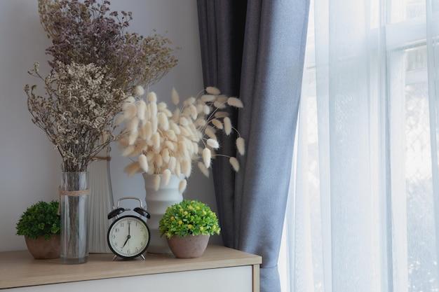Drewno stół z dekoracją kwitnie na białej zasłony tekstury nadokiennym tle.