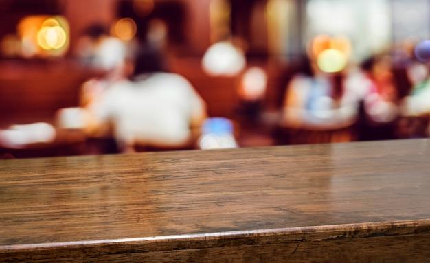 Drewno stół z ludźmi obiadowymi przy restauracyjnym plamy tłem