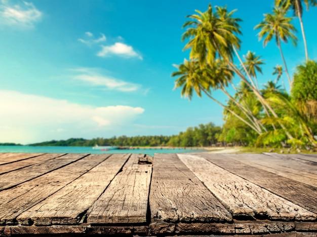 Drewno stół z zamazanym morzem i kokosowego drzewa tłem