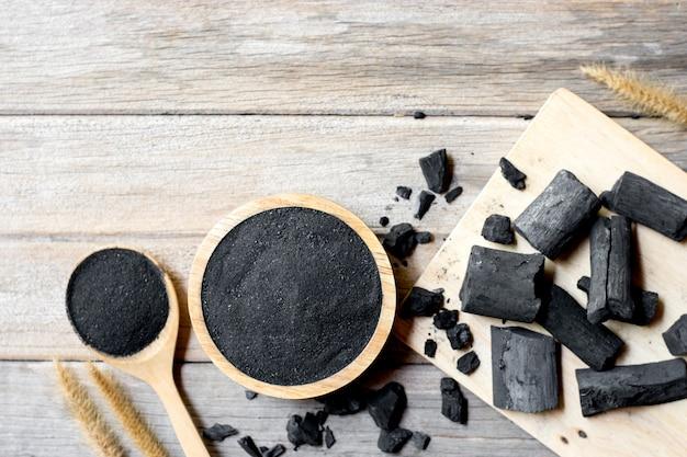 Drewno w proszku z węgla drzewnego, nałóż na filiżankę i umieść na białym stole.