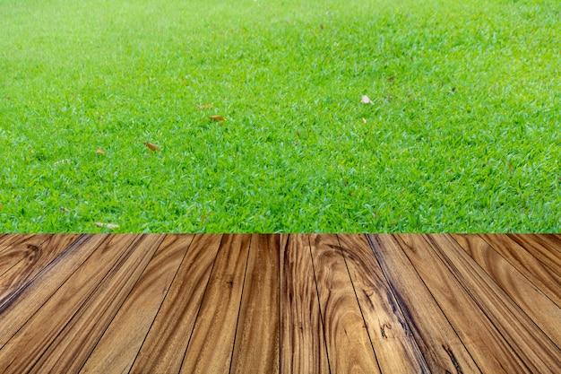 Drewno wierzchołka stołu wzoru perspektywa na zielonej trawy tle.