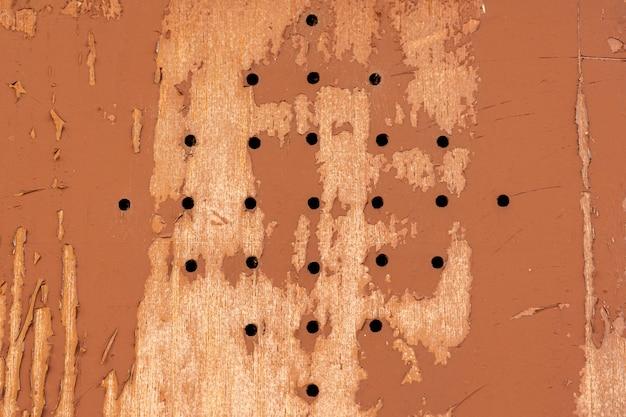 Drewno z otworami i rozdrobnioną farbą