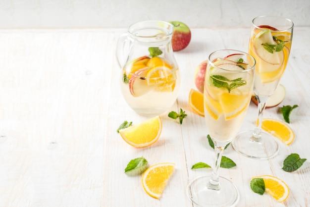 Drinki i koktajle. biała jesienna sangria z jabłkami, pomarańczą, miętą i białym winem. w kieliszkach do szampana, w dzbanku, na białym drewnianym stole. skopiuj miejsce