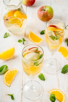 Drinki i koktajle. biała jesienna sangria z jabłkami, pomarańczą, miętą i białym winem. w kieliszkach do szampana, w dzbanku, na białym drewnianym stole.