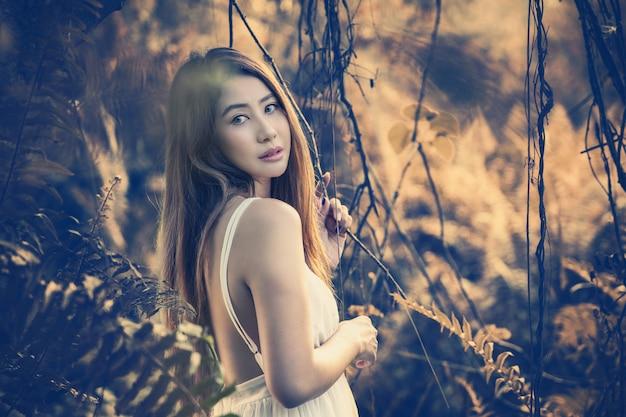 Drobna dziewczyna chodzi w mistycznym magicznym głębokim lesie.