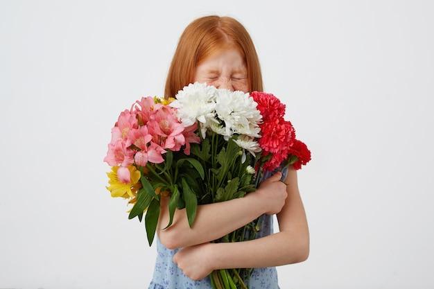 Drobna rudowłosa dziewczyna z piegami, zamknięta i uroczo wygląda, trzyma bukiet i rozkoszuje się zapachem kwiatów, nosi żółtą koszulkę, stoi na różowym tle.