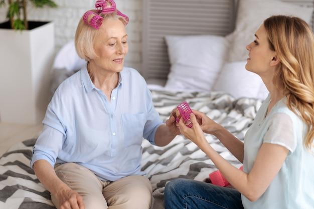 Drobna starsza kobieta z trzema różowymi wałeczkami we włosach, która ma zamiar wyjąć kolejny z rąk córki