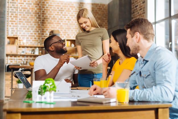 Drobne błędy. czterech wesołych, zajętych i szczęśliwych uczniów rozmawia o błędach, zastanawiając się, jak je naprawić
