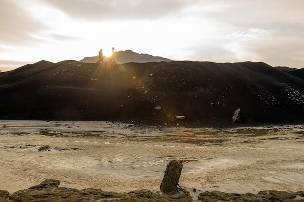 Drobne sylwetki dwóch ekologów lub badaczy poruszających się wzdłuż szczytu wzgórza na tle szarego pochmurnego nieba z jasnym słońcem o zachodzie słońca
