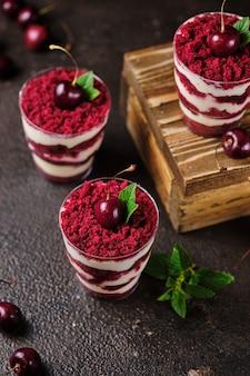 Drobny czerwony aksamit z kremem serowym i żelami wiśniowymi. deser przyozdobiony świeżymi wiśniami i miętą.