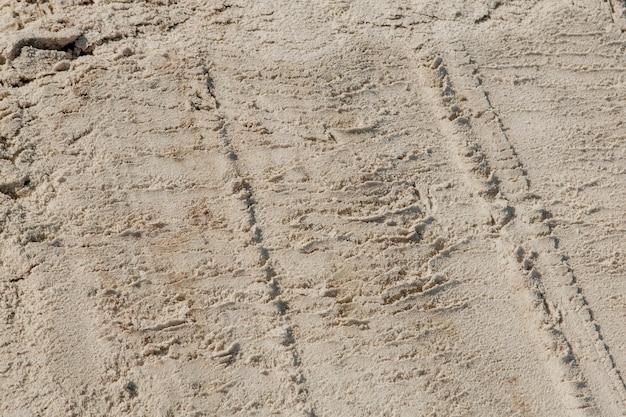 Drobny piasek na plaży w letnim słońcu.
