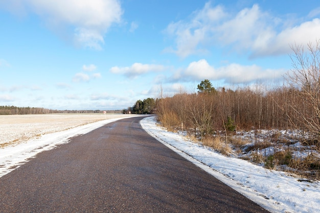 Droga asfaltowa oddzielająca las od pola uprawnego. niebieskie niebo.