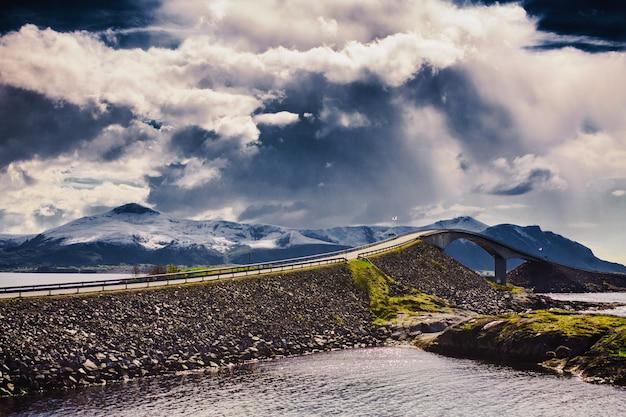 Droga atlantycka w norwegii. podróżuj po europie. most nad fiordem w norwegii. piękny wiosenny krajobraz w skandynawii. turystyka w europie. charakter tła. piękny krajobraz z drogą