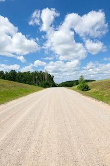 Droga bez asfaltu, sfotografowana w letni dzień. pochmurna pogoda. wieś. na wyżynach rastu upraw rolnych