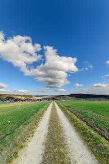 Droga biegnąca między dwoma dużymi zielonymi krajobrazami pod błękitnym niebem