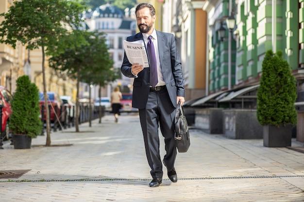 Droga do pracy. wesoły dorosły człowiek idąc ulicą, czytając gazetę