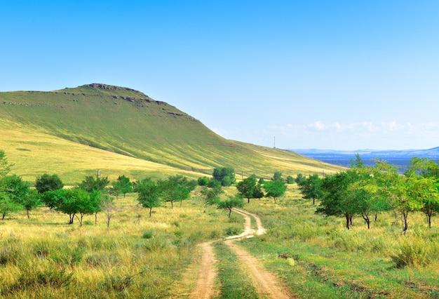 Droga gruntowa na zbocza góry pod błękitnym niebem terytorium krasnojarska syberia rosja