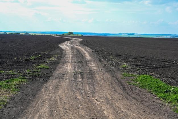 Droga gruntowa odchodząca po horyzont. rolnictwo zaorane pole. czarna gleba zaorane pole. ziemia uprawna przygotowana pod sadzenie roślin. żyzna gleba w ekologicznym gospodarstwie rolnym. krajobraz gruntów rolnych.