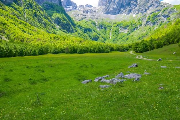 Droga gruntowa przez malowniczą równinę wśród wysokich gór.