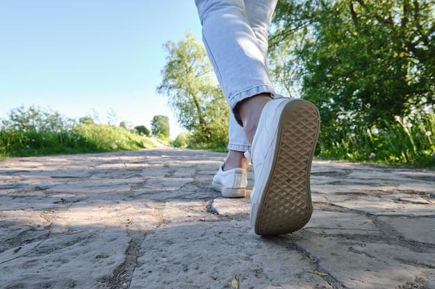 Drogą idzie mężczyzna. zbliżenie stopy. widok z dołu, widok z tyłu.