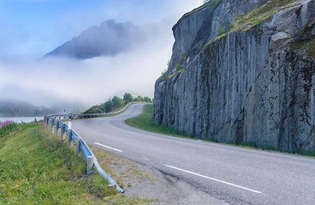 Droga jest wygięta wokół klifu na tle gór, norwegia