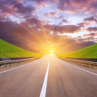 Droga między górami z łąkami i zachodem słońca
