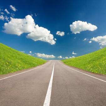 Droga między letnimi wzgórzami a błękitnym niebem