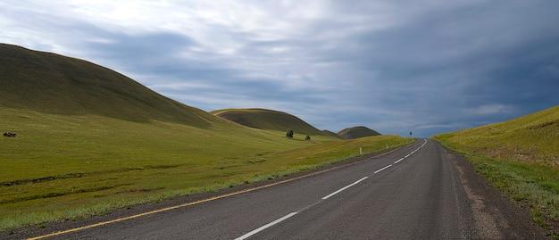 Droga między wzgórzami i pięknym pochmurnym niebem.