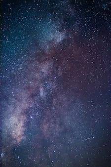 Droga mleczna. fantastyczny nocny krajobraz z purpurową drogą mleczną, niebo pełne gwiazd, błyszczące gwiazdy.