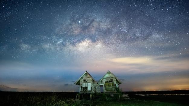 Droga mleczna galaxy z bliźniaczymi domami w wiosce pakpra, prowincja phatthalung, tajlandia