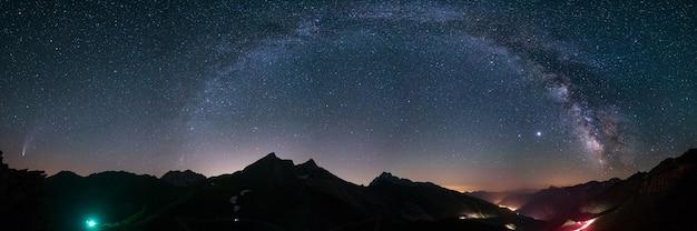 Droga mleczna i gwiazdy na nocnym niebie nad alpami. znakomita kometa neowise świecąca na horyzoncie po lewej stronie. panoramiczny widok, astrofotografia, obserwacja gwiazd.