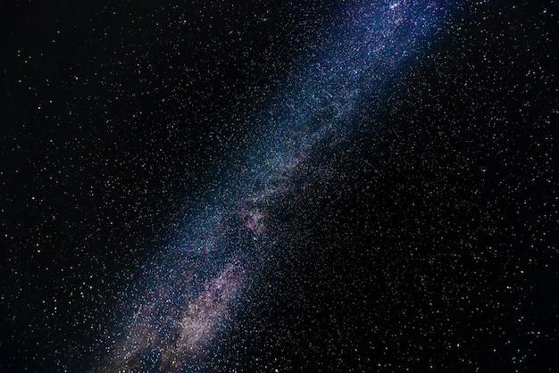 Droga mleczna na niebieskim gwiaździstym niebie w nocy.