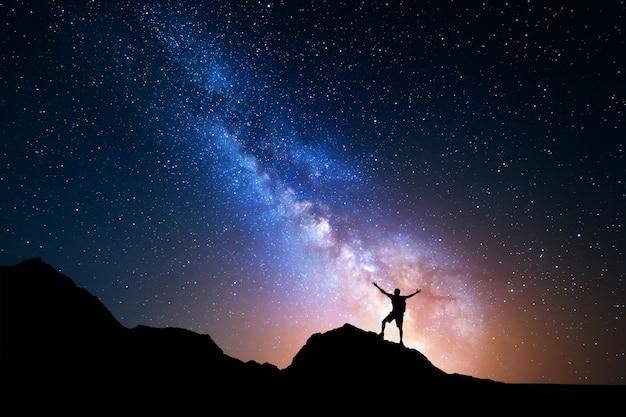 Droga mleczna. nocne niebo i sylwetka człowieka stojącego