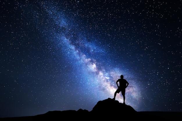 Droga mleczna. nocne niebo z gwiazdami i sylwetka szczęśliwego człowieka z plecakiem.