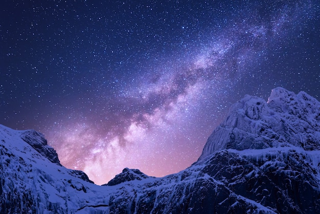 Droga mleczna ponad zaśnieżonymi górami. przestrzeń. fantastyczny widok ze śniegiem pokryte skałami i gwiaździste niebo w nocy w nepalu. grzbiet górski i niebo z gwiazdami w himalajach.