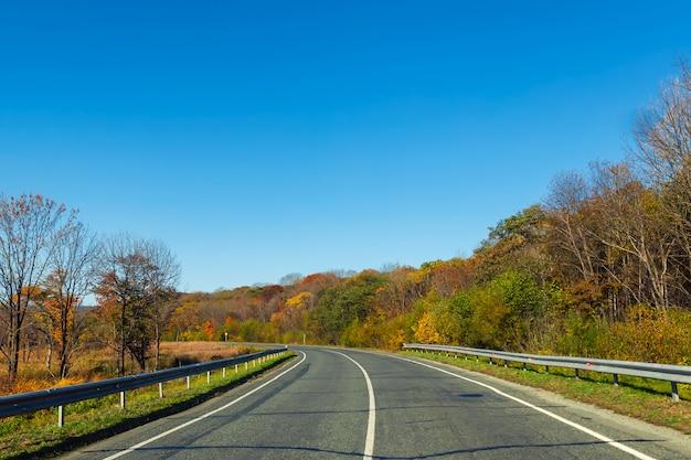 Droga na wsi z piękną przyrodą w sezonie jesiennym i jasne błękitne niebo