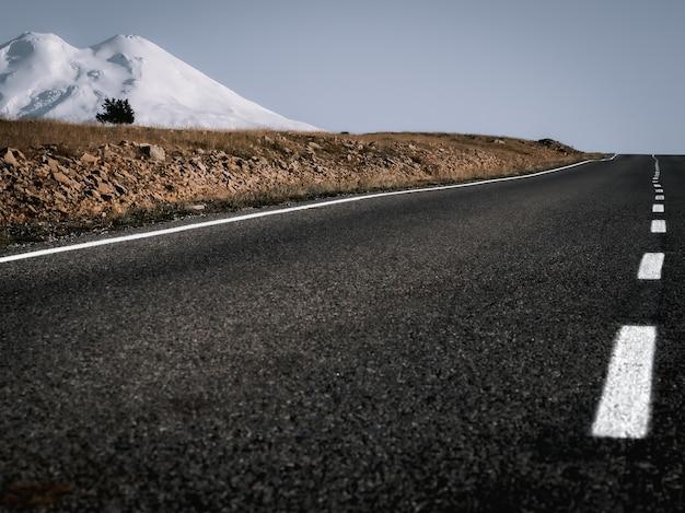 Droga odchodząca w dal czarny asfalt i jasne białe oznaczenia jezdni