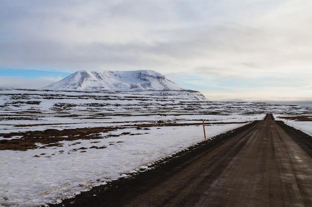 Droga otoczona polem i skałami pokrytymi śniegiem pod zachmurzonym niebem w islandii