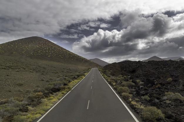 Droga otoczona wzgórzami pod zachmurzonym niebem w parku narodowym timanfaya w hiszpanii