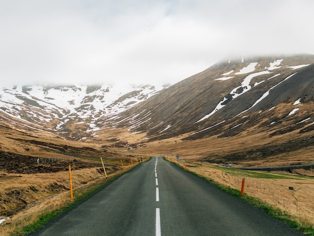 Droga otoczona wzgórzami pokrytymi zielenią śniegu i mgły na islandii