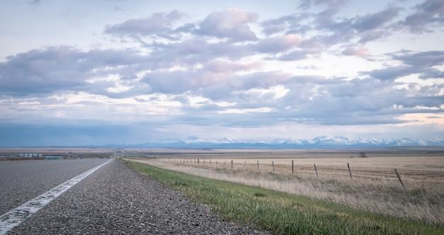 Droga prowadząca do horyzontu z górami w tle, podczas zachodu słońca w południowej albercie w kanadzie