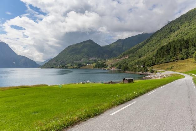 Droga prowadząca do tajemniczego wąwozu otoczonego chmurami gór norweskich.