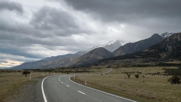 Droga prowadząca w kierunku gór z pochmurnym niebem, wysoka perspektywa, wykonana w nowej zelandii