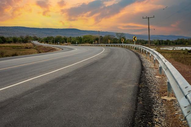Droga prowadzi do pięknych gór i nieba o zachodzie słońca