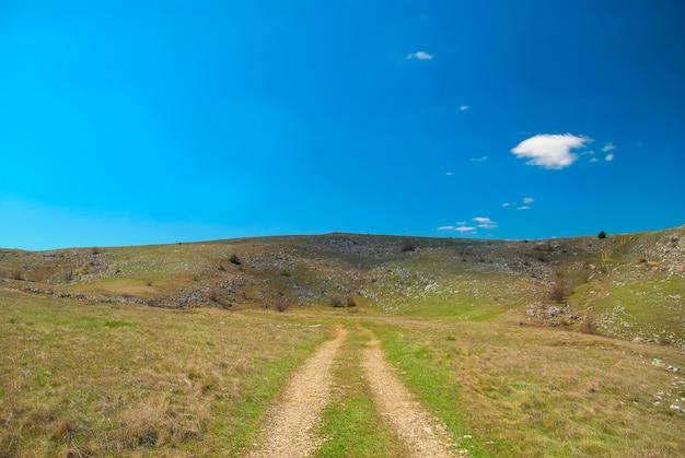 Droga przez wzgórza z chmurami i niebieskim niebem.